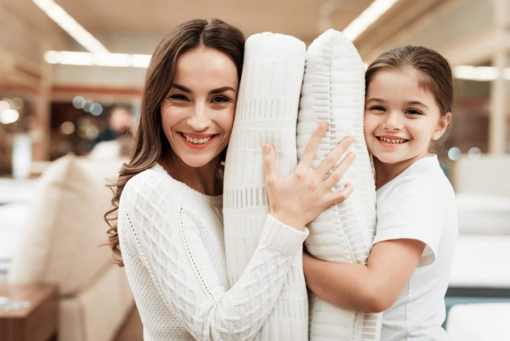 happy mother and daughter hugging pillows