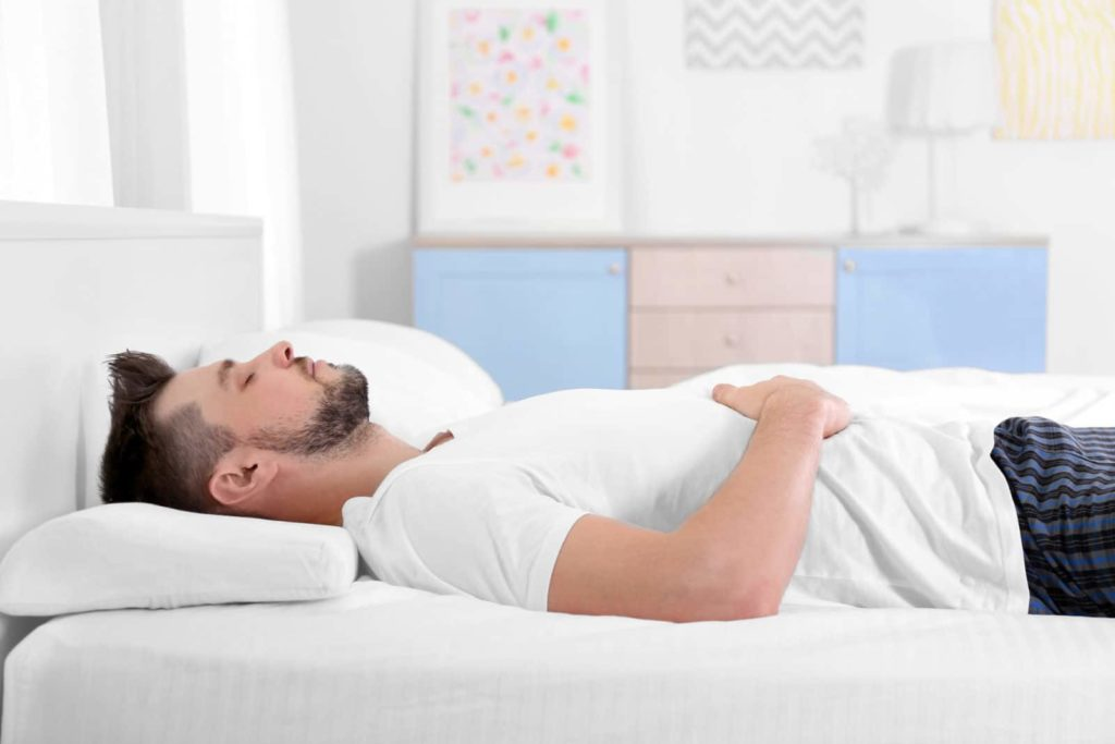 man using a memory pillow while sleeping on his back