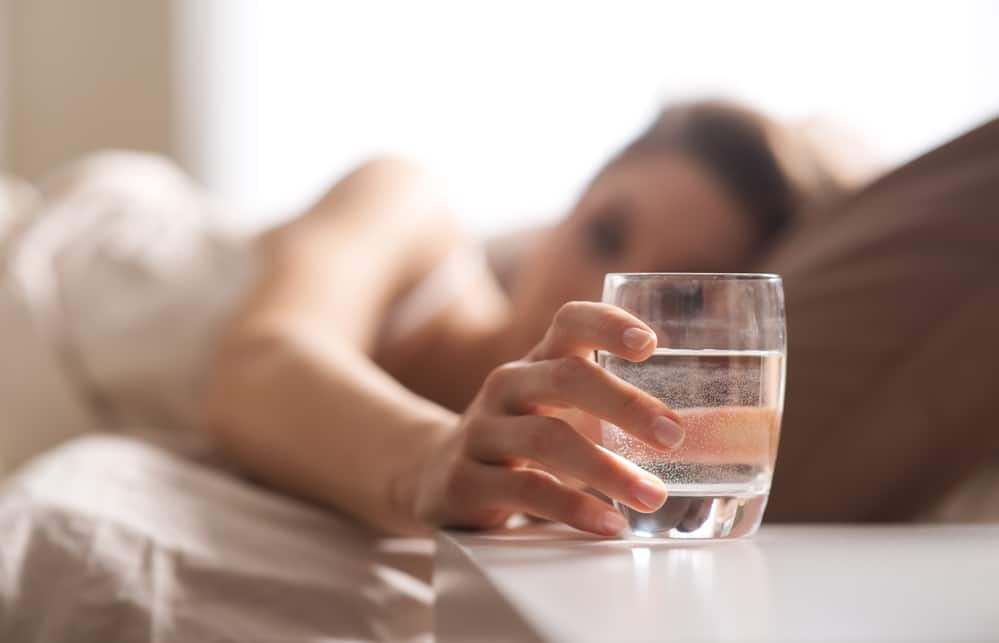 woman having a glass of water before bed