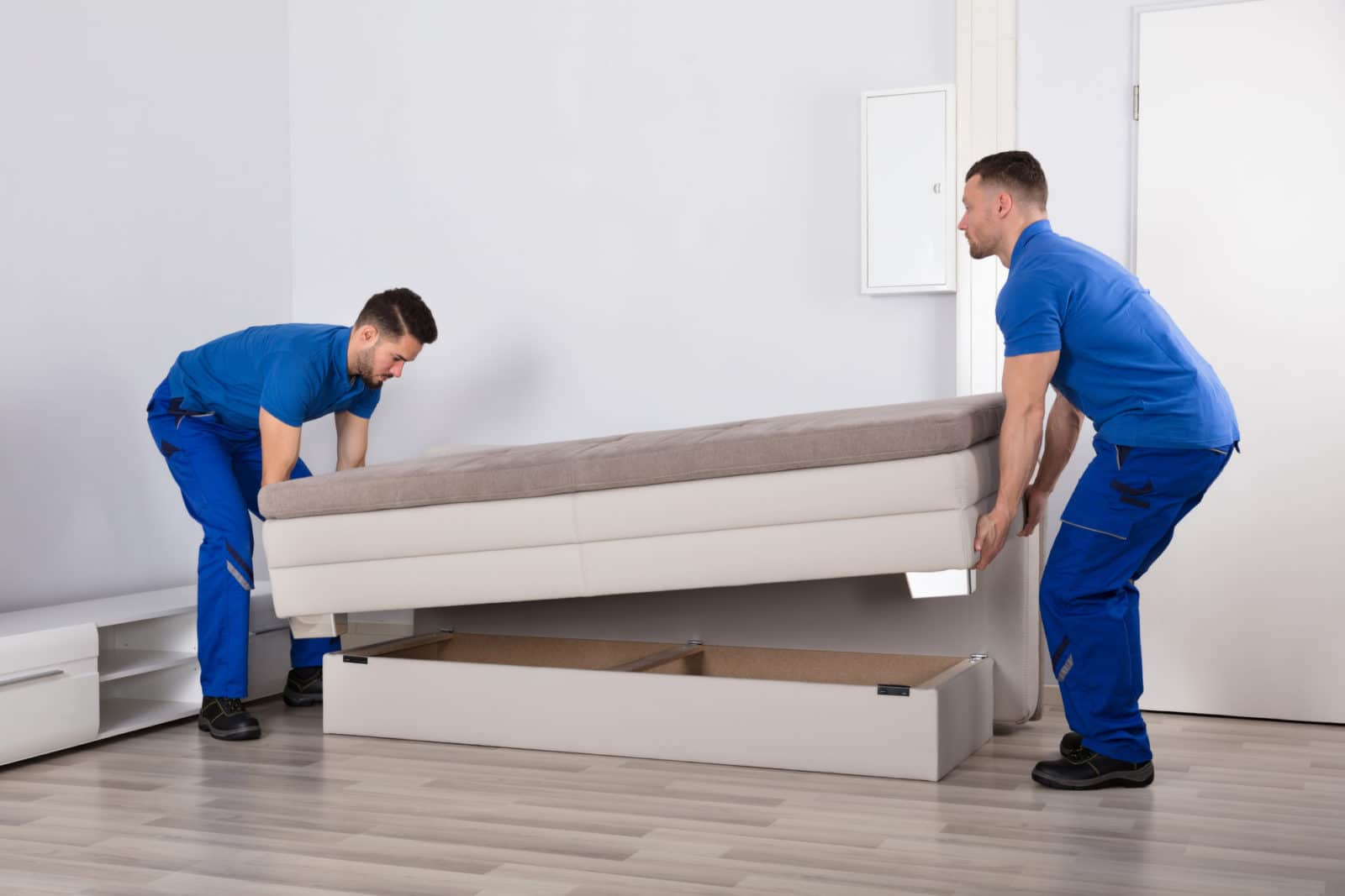 two movers bend their knees to lift a sofa