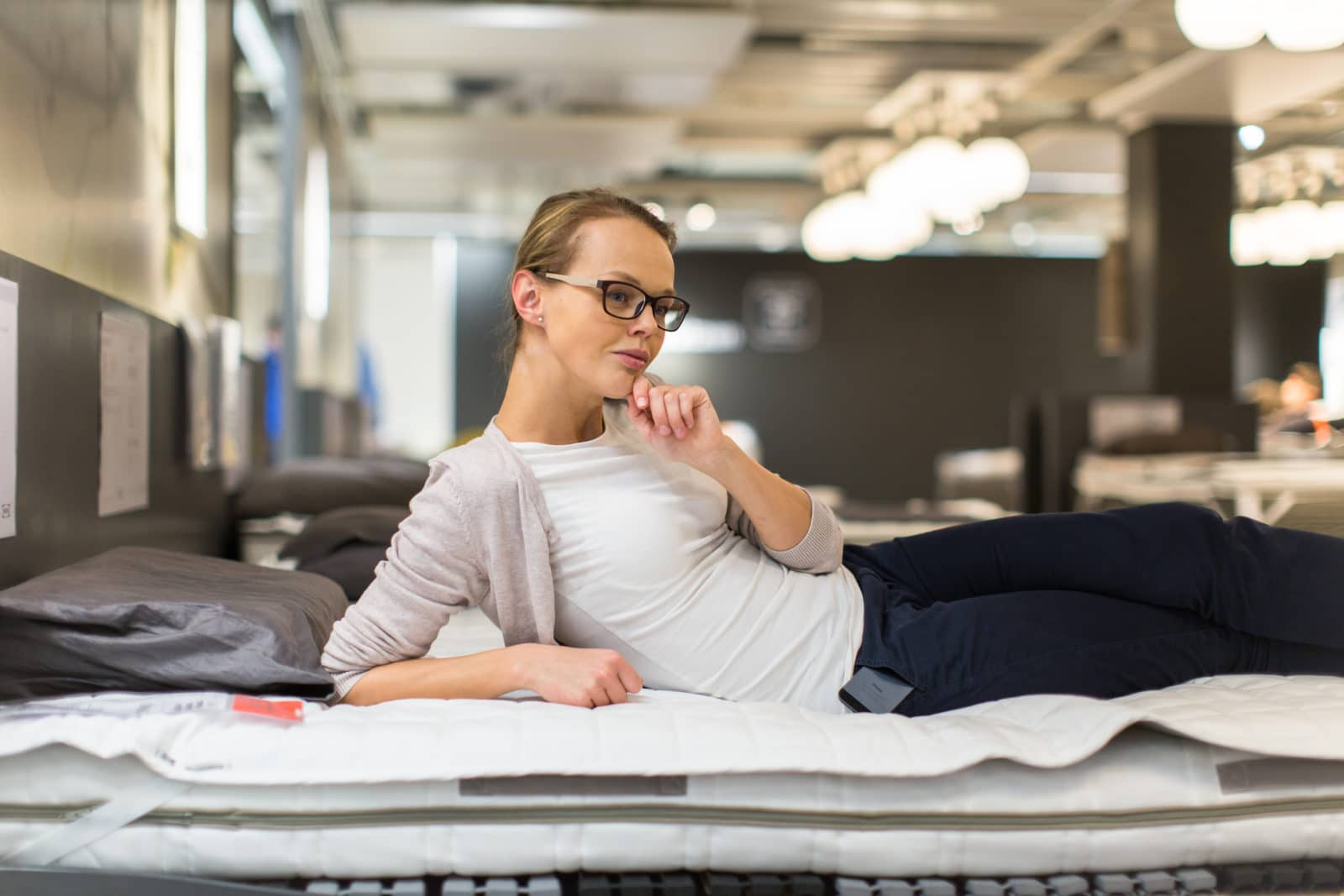 woman thinking about buying the right mattress