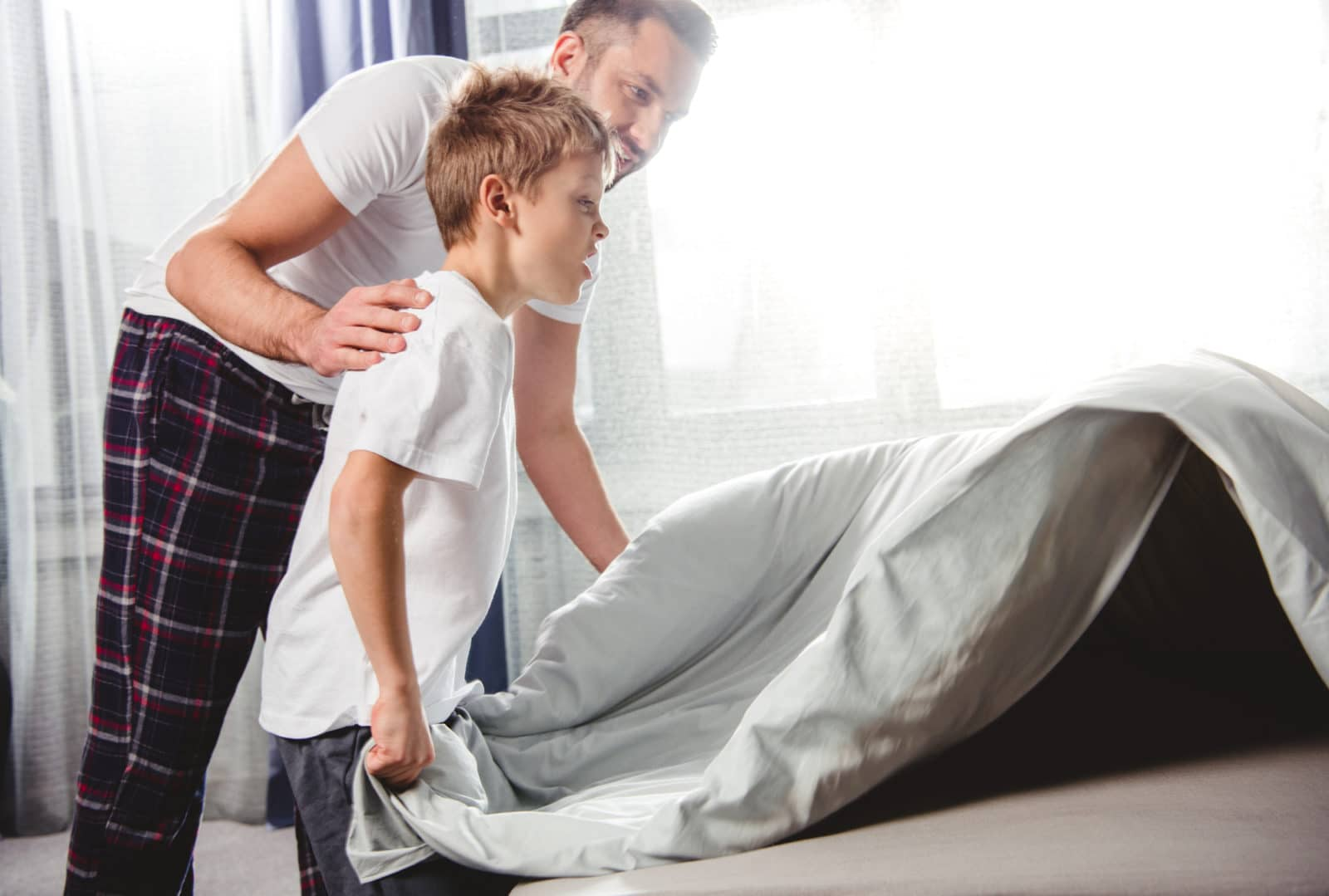 father and son making the bed