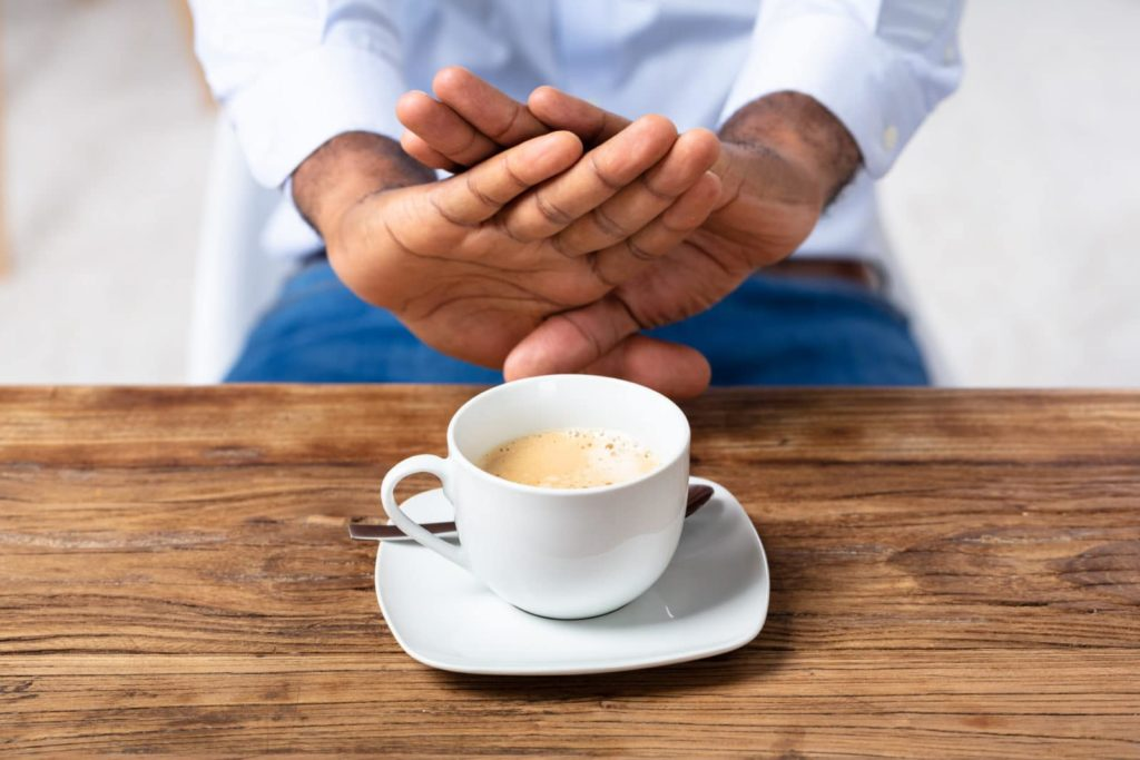 man refusing a cup of coffee