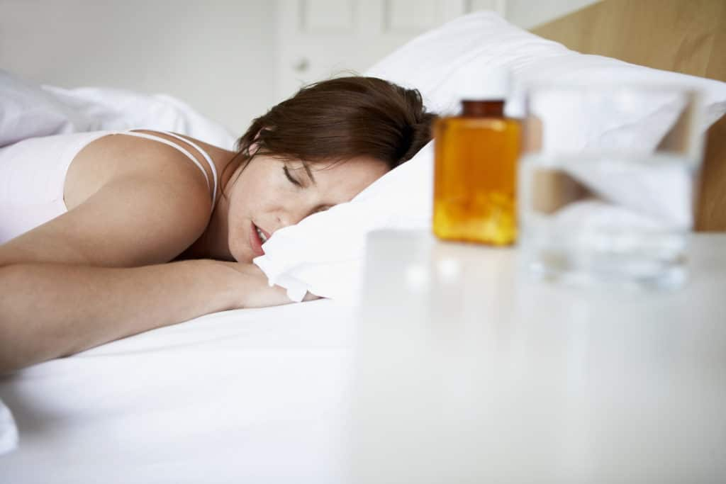 sleeping woman with a bottle of pills nearby