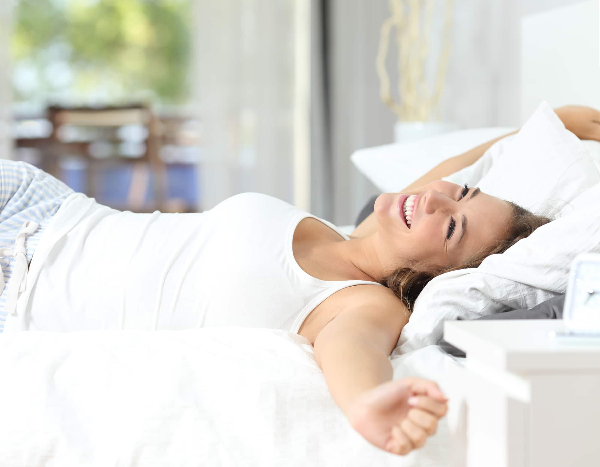 a woman waking up with a smile