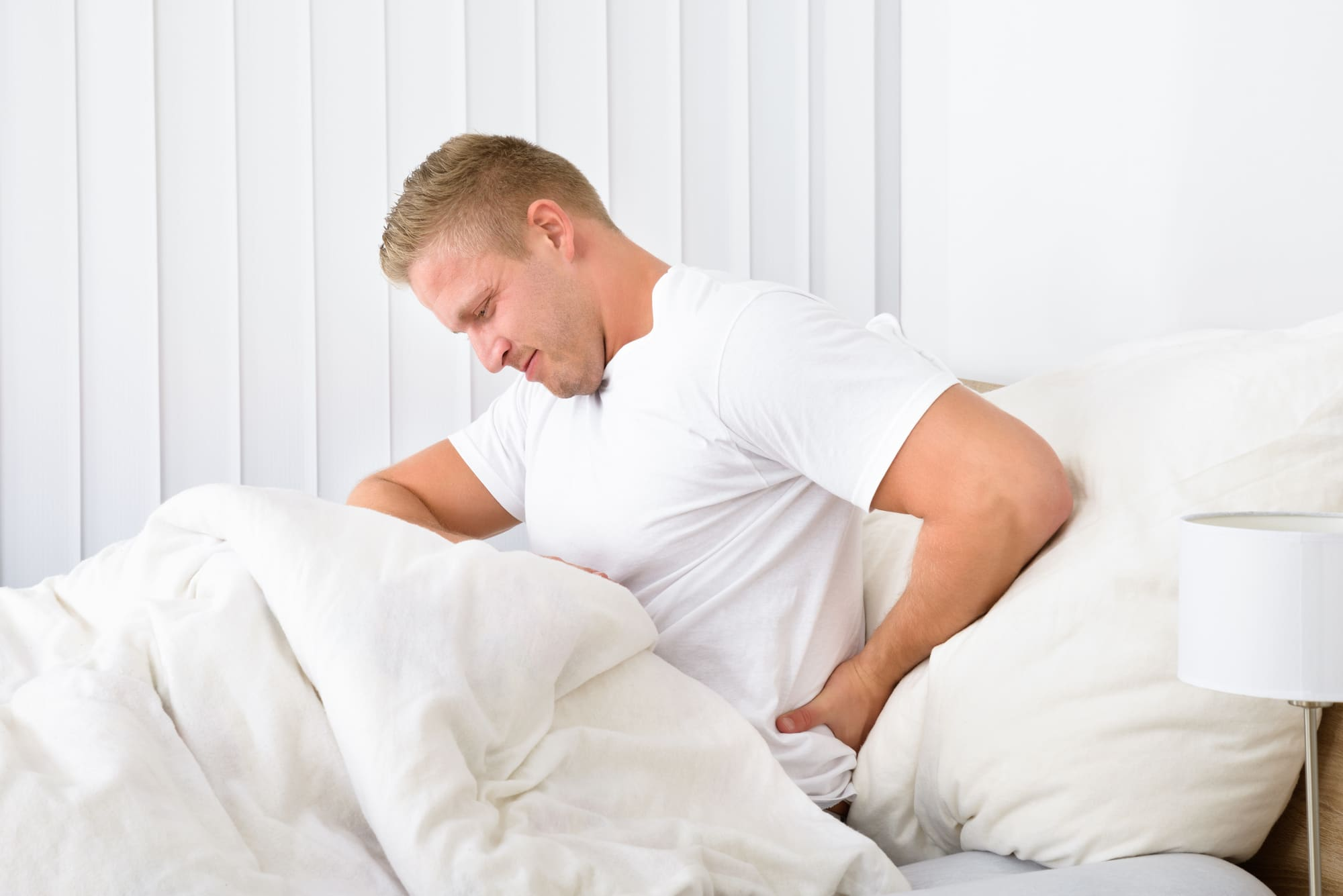 man on bed suffering discomfort
